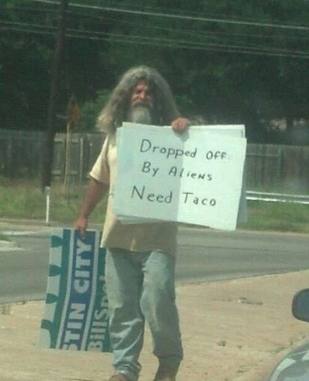 Dropped Off By Aliens - Funny Photo - homeless guy holding funny sign