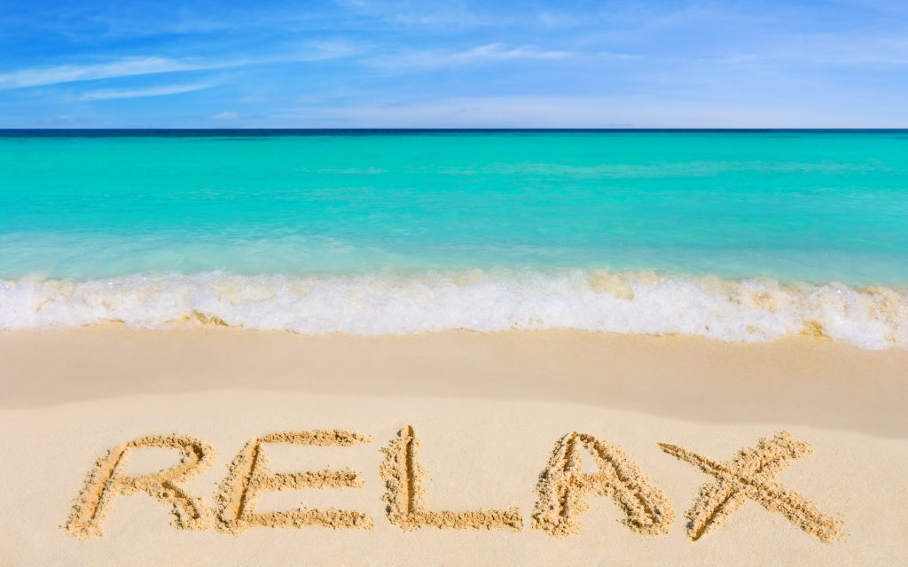 """Beach Wallpaper with """"Relax"""" written in the sand"""
