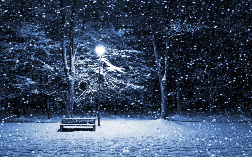 The Snowy Park Wallpaper - A snow covered park at night, with a light shining down on a snow covered park bench.